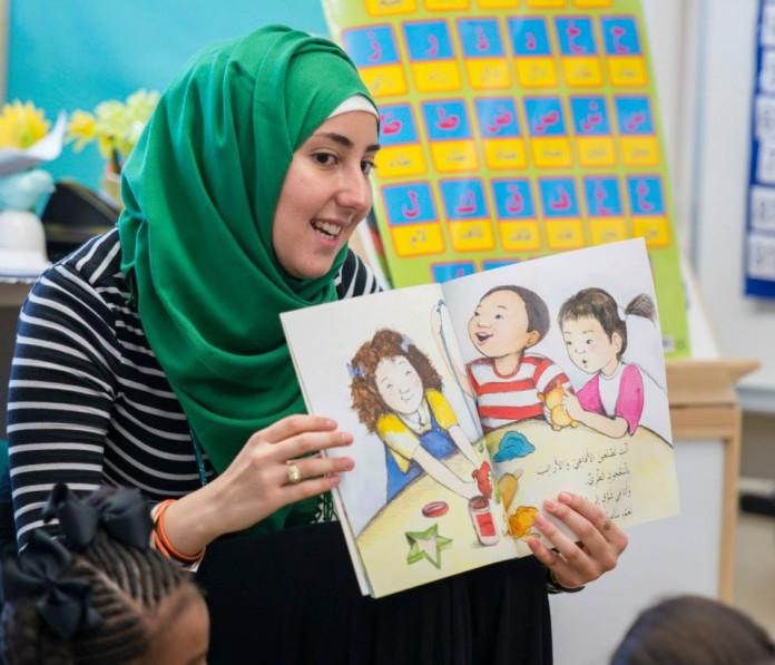 Una mujer con la cabeza cubierta sostiene un libro frente a unos niños (Foto cedida por AIMS)