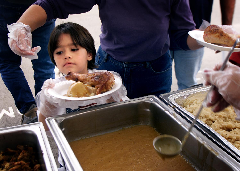 Criança voluntária serve jantar de Ação de Graças em evento comunitário (© Getty Images)