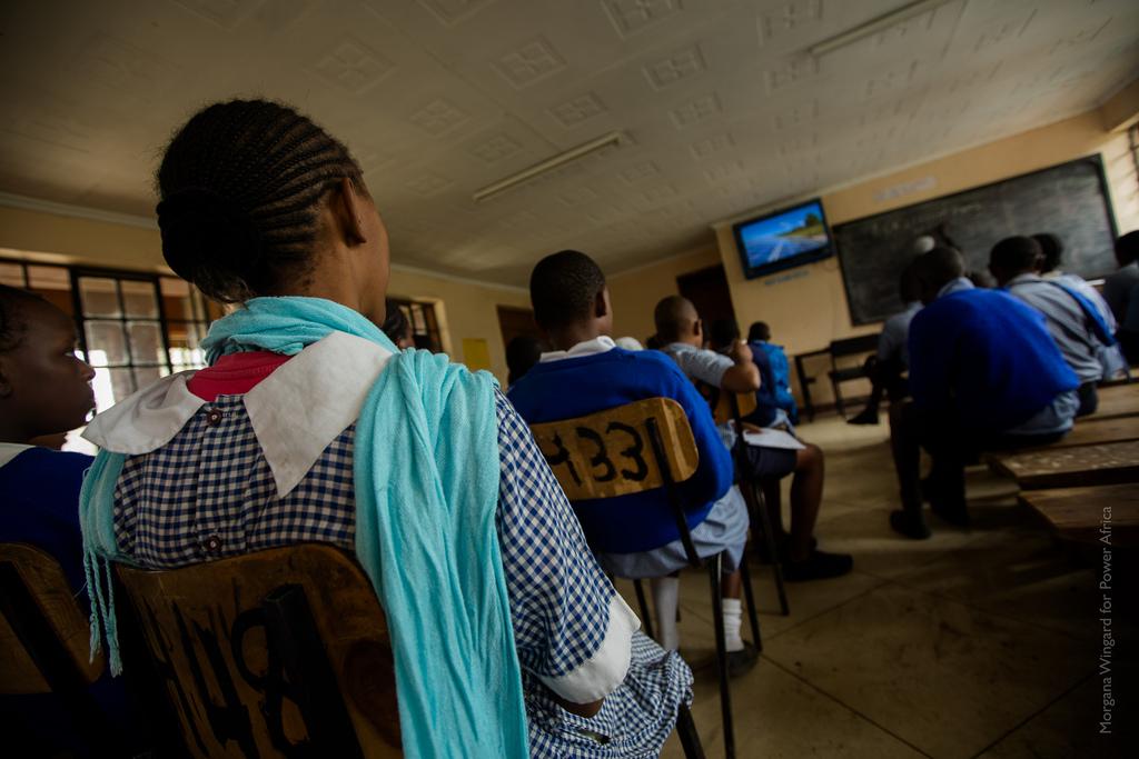 Des élèves vus de dos, assis dans une salle de classe, regardant un écran de télé. (Crédit Morgana Wingard/Power Africa)