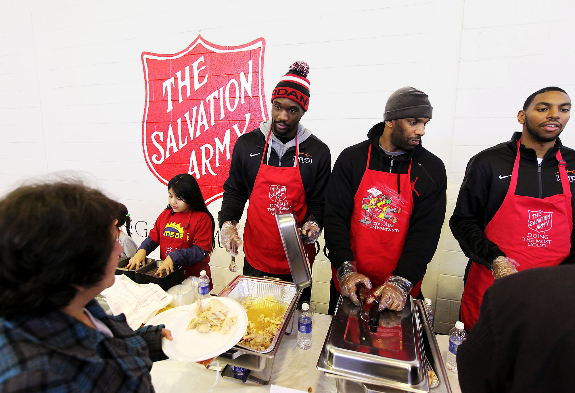 College basketball players serving food at a community center on Thanksgiving Day (© AP Images)