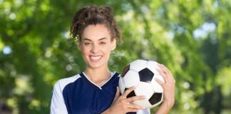 Jugadora de fútbol sosteniendo un balón (Thinkstock)