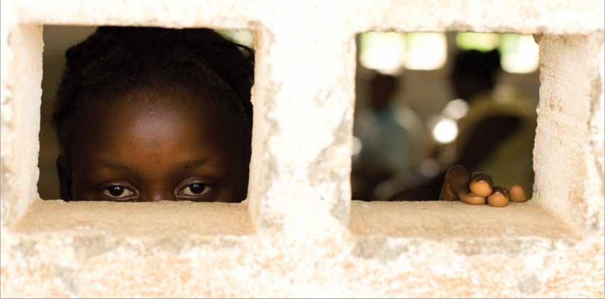 Girl looking out window of cement building (© UNICEF/NYHQ2010-0670/Olivier Asselin)