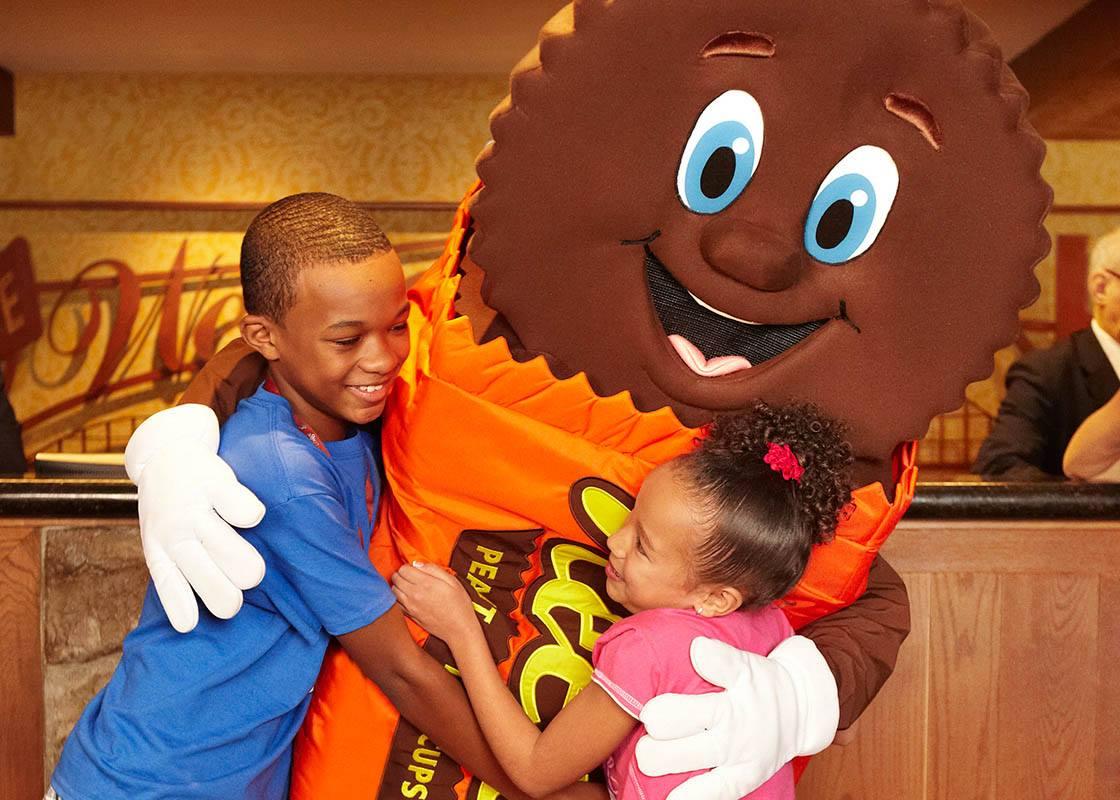 Duas crianças abraçam mascote na área de diversões do Parque Hershey (Cortesia: Parque Hershey/Facebook)