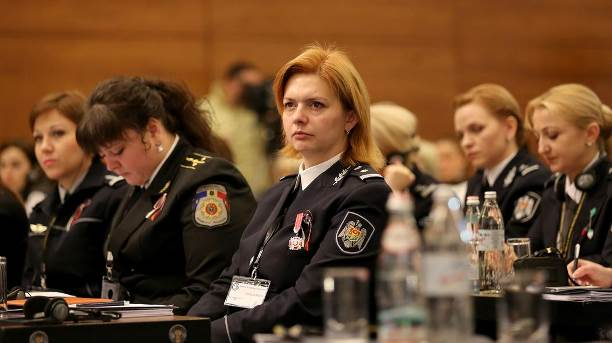 Women police officers seated in room. (State Dept.)