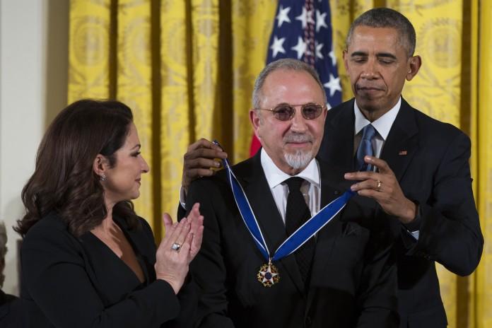 Le président Obama mettant une médaille autour du cou d'Emilio Estafan, avec Gloria Estefan debout à côté de lui (© AP Images)