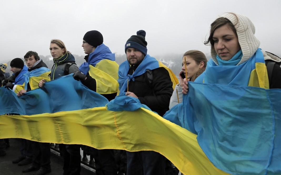 Fila de personas de pie envueltas en la bandera ucraniana (© AP Images)