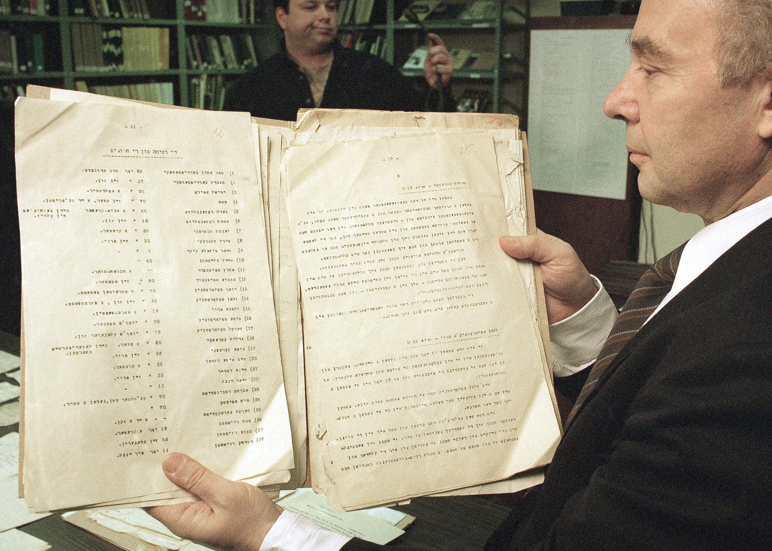 Hombre sosteniendo documentos históricos amarillentos (© AP Images)