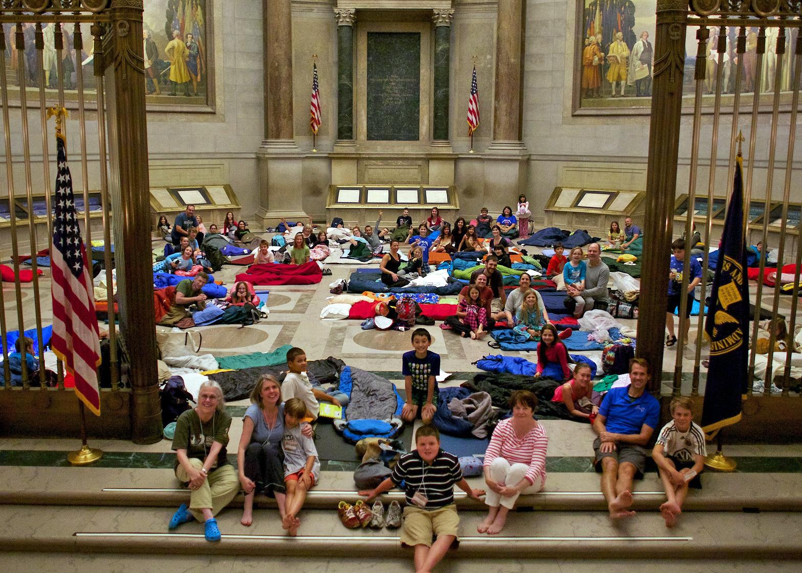 Personas sentadas en el suelo con sacos de dormir en la Rotonda de los Archivos Nacionales (Archivos Nacionales de Estados Unidos)
