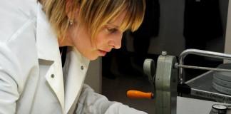 زنی که کت و دستکش های سفید پوشیده در حال آزمایش یک حلقه فیلم است. (بایگانی ملی ایالات متحده)