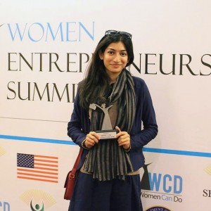 Hira Batool Rizvi holding trophy in front of Women Entrepreneurs Summit sign (Courtesy of Hira Batool Rizvi)