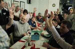 Grand groupe de personnes autour d'une table, beaucoup d'entre elles lèvent la main pour voter (© AP Images)