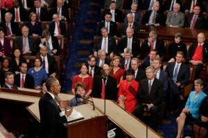 Barack Obama derrière un pupitre et face à un auditoire, debout (© AP Images)