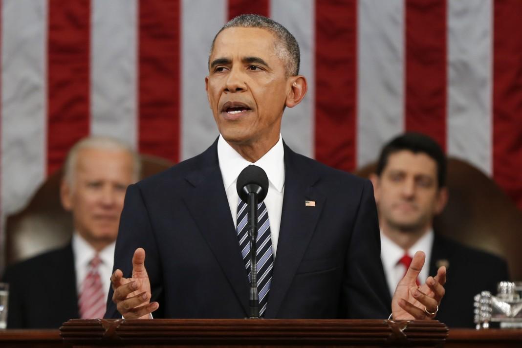 Le président Obama debout, avec le vice-président derrière lui à sa droite et le président de la Chambre des représentants derrière lui à sa gauche, le drapeau américain à l'arrière-plan (© AP Images)