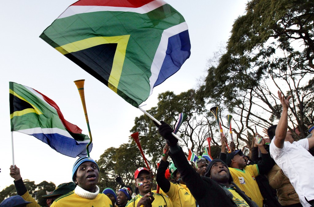 Soccer fans wave South African flags at the 2010 World Cup. (© AP Images)