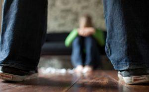 Orang yang duduk dilihat di antara kaki berdiri di atas lantai kayu (© Thomas Imo/Alamy)