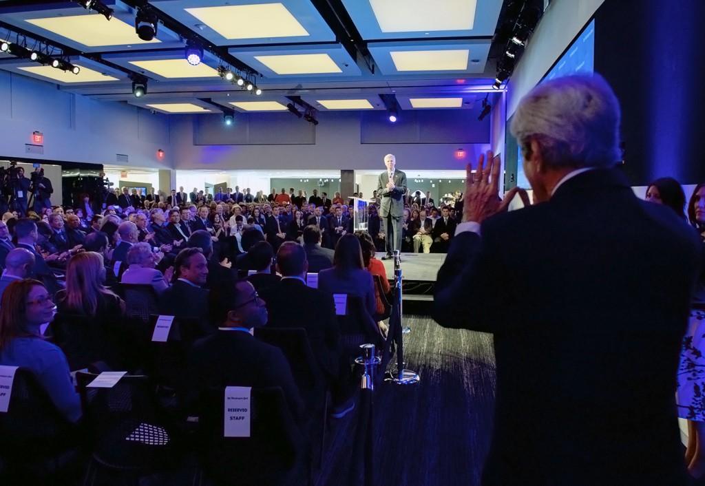 جان کری برای جمعی که نشسته اند دست تکان می دهد. (وزارت امور خارجه)