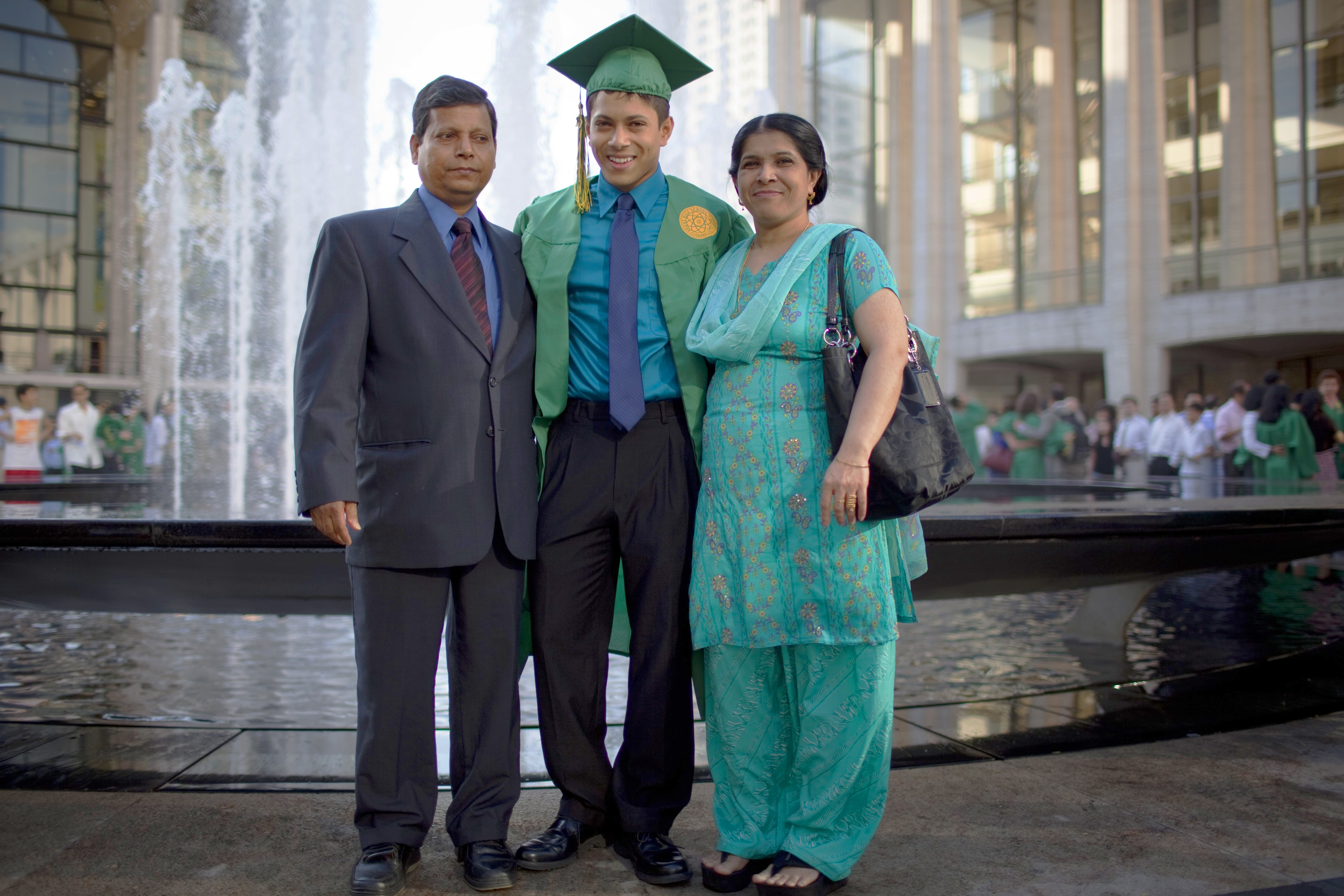 Joven adulto con toga de graduación y birrete posando junto a sus padres al frente de una fuente (© Getty Images)