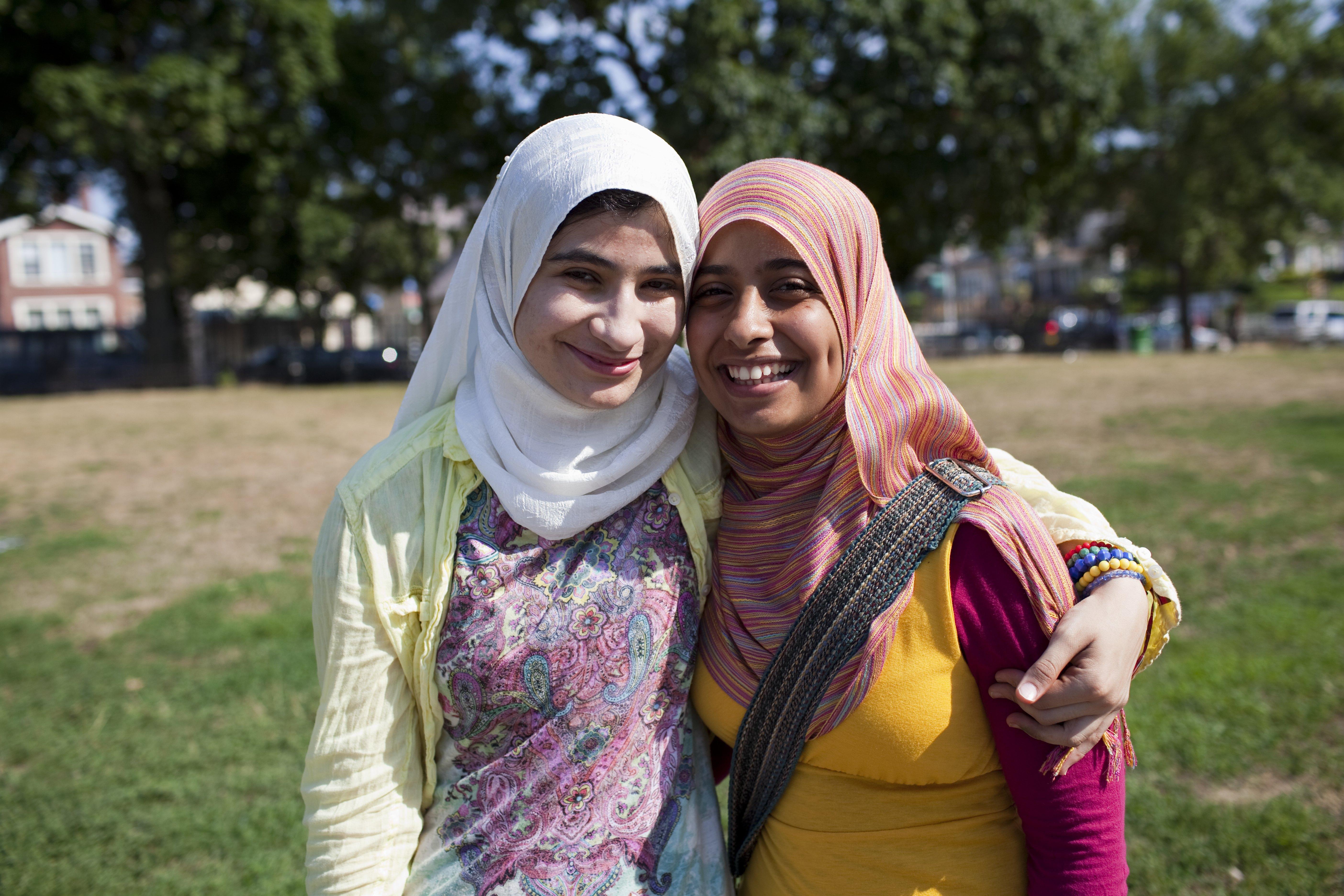 Dos mujeres jóvenes con tocados sonríen y posan para la cámara al aire libre. (© Getty Images)