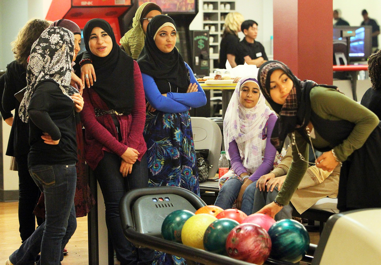Grupo de mujeres jóvenes con pañuelos en una pista de bolos. (© Getty Images)