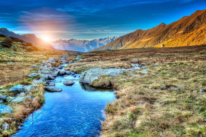 Vue d'une prairie, le soleil se couchant derrière les montagnes (Shutterstock)