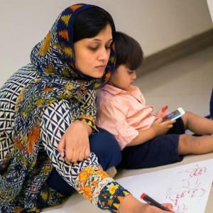 یک زن روی کاغذ می نویسد؛ کودکی کنار او نشسته است. (عکس از مدیحه حمید)
