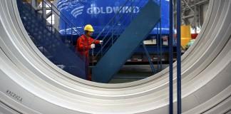 کارگری در حال هُل دادن یک پلکان قابل حمل از مقابل یک ژنراتور بادی بسیار بزرگ است. (عکس از آسوشیتدپرس)