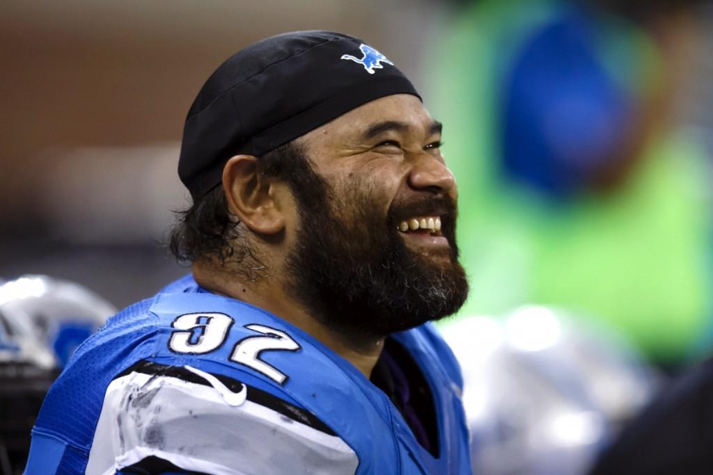 Hombre sonriente en uniforme de fútbol americano (© AP Images)