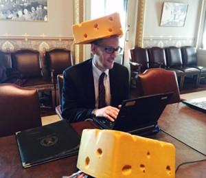 رجل يجلي حول طاولة مرتديًا قبعة تبدو وكأنها كتلة جبن. (White House)