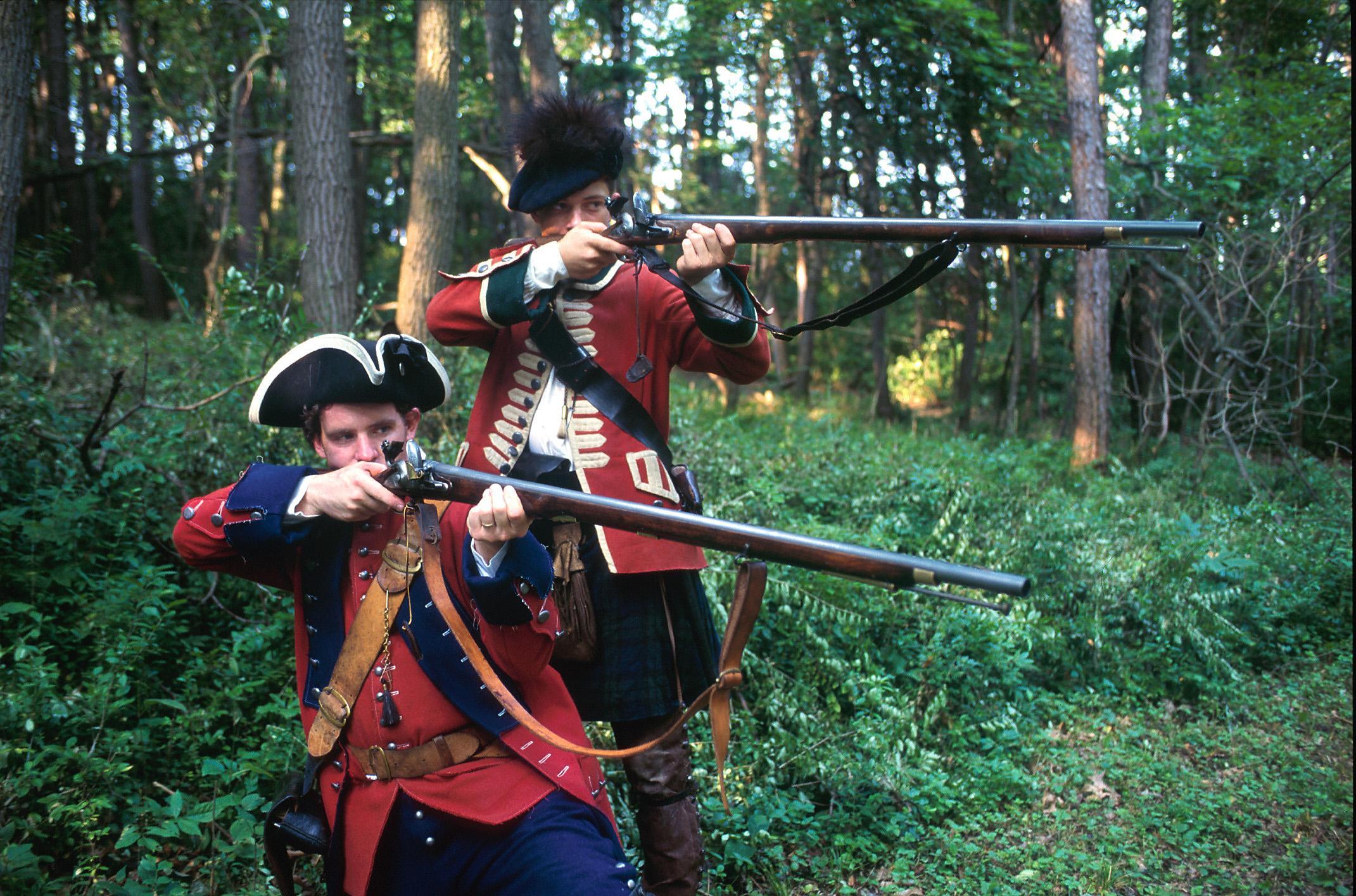 ممثلون يلعبون دور جنود في الحرب الثورية يحملون بنادق (State Dept.)
