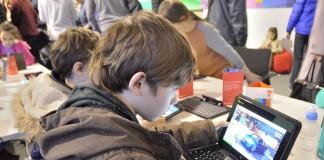کودکانی که دور میز نشسته و به کامپیوتر های لپ تاپ نگاه می کنند. (Shutterstock)