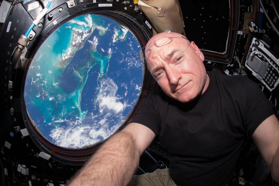Scott Kelly se toma una selfi junto a una escotilla desde la que se ve la Tierra (NASA)