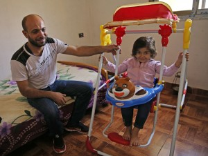 Man sitting on bed and young girl using toy (© AP Images)
