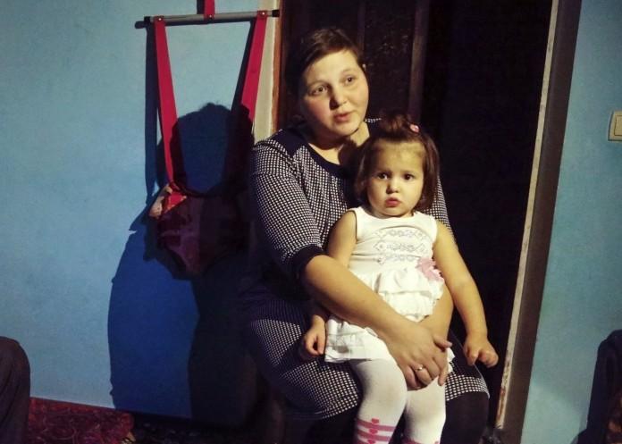 Une femme assise, une jeune enfant sur les genoux (© AP Images)