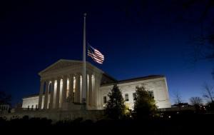 پرچم ایالات متحده که در برابر یک ساختمان ساخته شده به سبک کلاسیک به حالت نیمه افراشته درآمده است. (© عکس از آسوشیتدپرس)