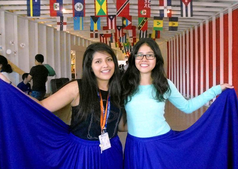 Dos muchachas adolescentes posan para la cámara en una sala en la que cuelgan banderas del techo (Foto cedida por Cinthya Alvarado)