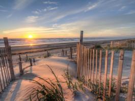 نمایی از طلوع آفتاب از ساحلی با تپه های شنی و نرده های چوبی نصب شده بر روی شن ها (Thinkstock)