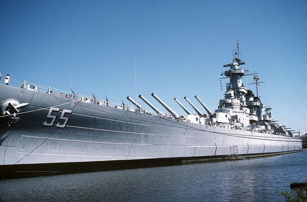 Grand navire à quai dont les grands canons sont dirigés vers le ciel (U.S. Navy/Don S. Montgomery/Creative Commons)