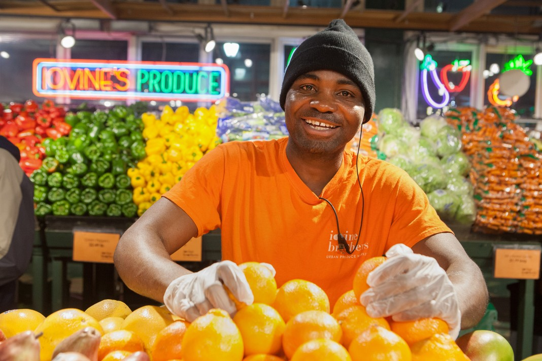 مرد جوانی در حال چیدن میوه در یک مغازه خواربار فروشی (وزارت امور خارجه/دی . ای. پیترسون)