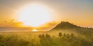 El sol iluminando la niebla en un panorama arbolado con una pequeña montaña al fondo (Foto cedida por East Bali Cashews)