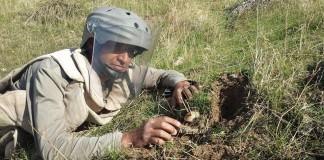 عراقی که لباس محافظتی پوشیده و روی علف ها دراز کشیده است و روی مین های کارگذاشته شده کار می کند (گروه مشورتی مین ها)