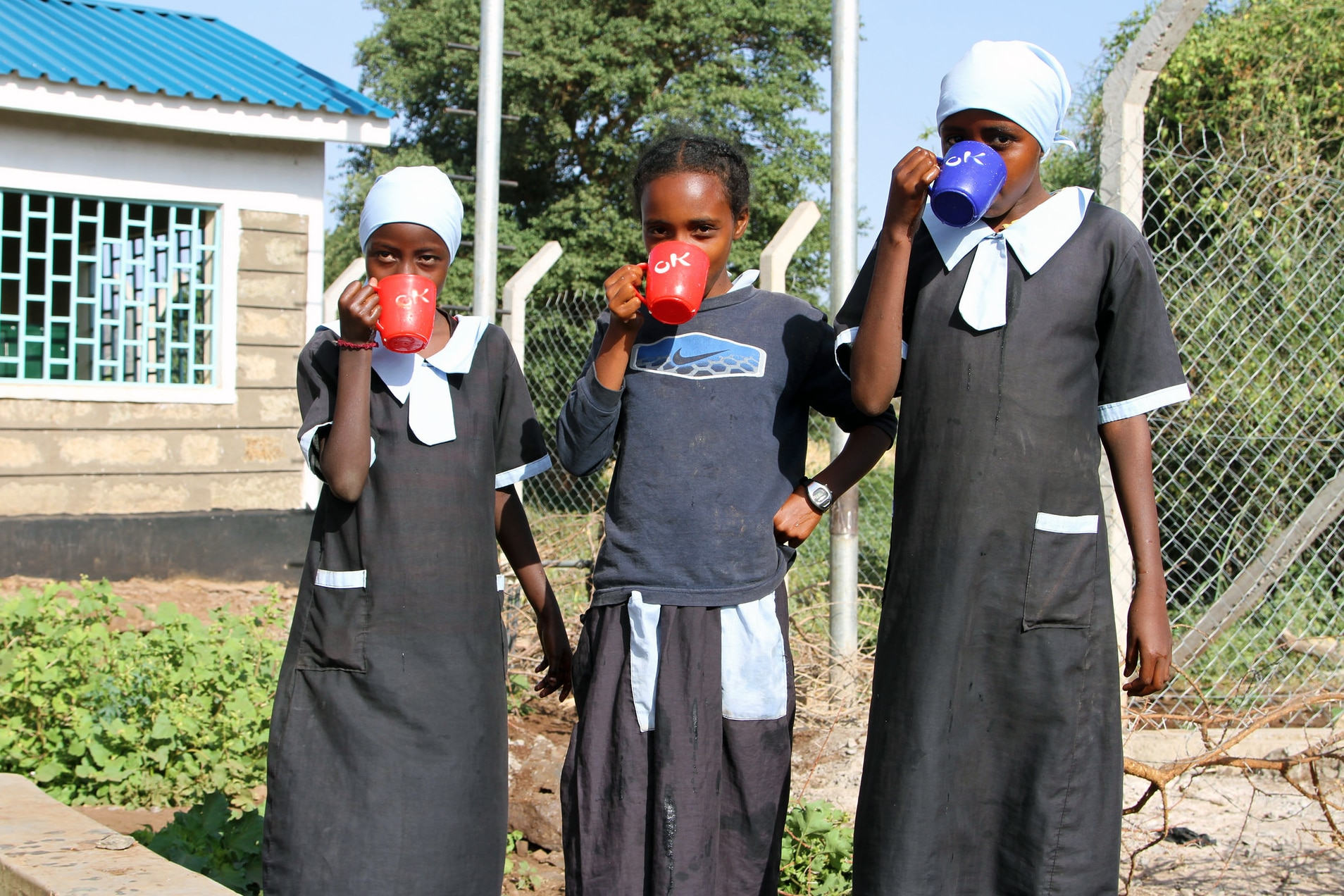 Three girls drinking water from mugs; vegetable garden and building in background (USAID)