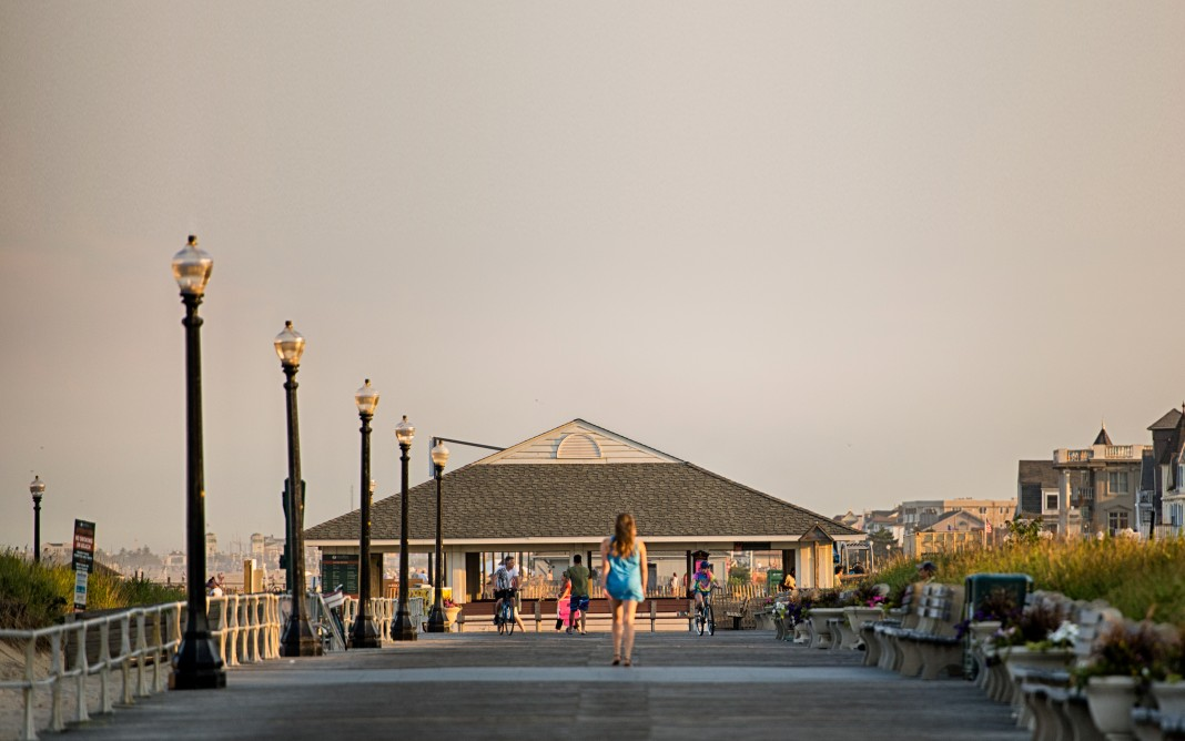 Woman walking down a boardwalk toward a pavilion (Nathan Siemers via Flickr)