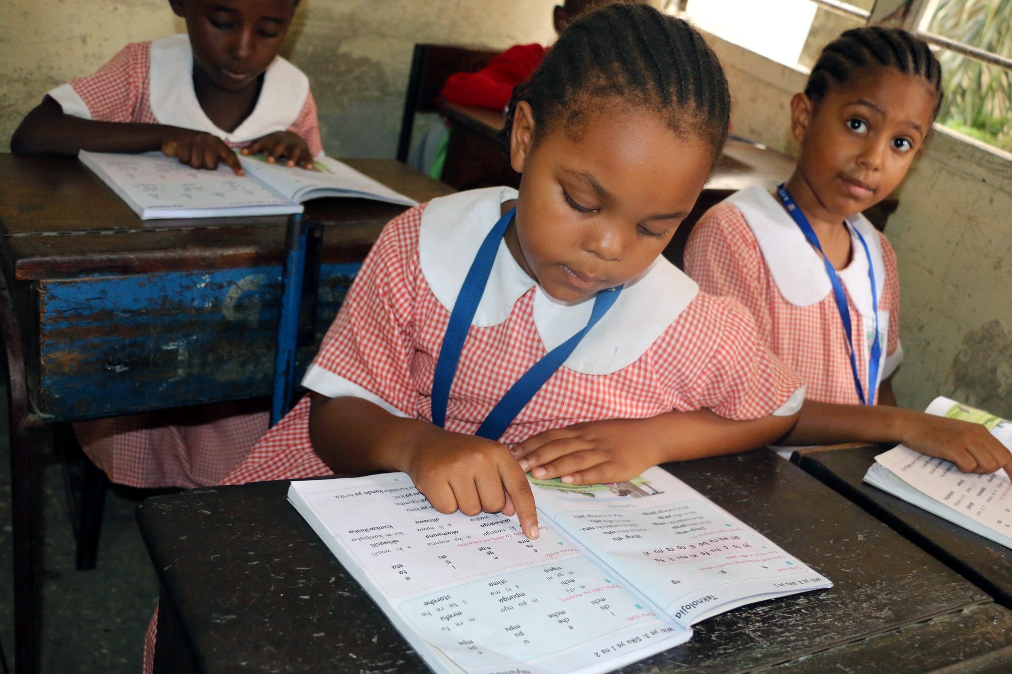 Three young girls in school uniforms, seated at desks with notebooks (USAID)