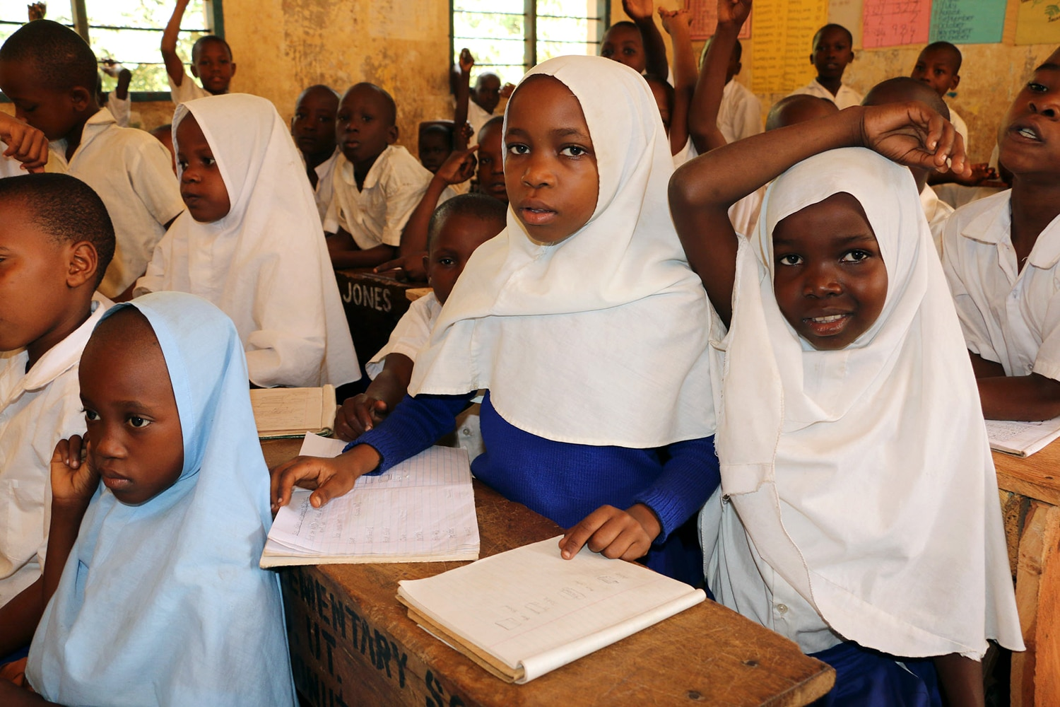 Classroom of young girls in headscarves, at desks with notebooks (USAID)