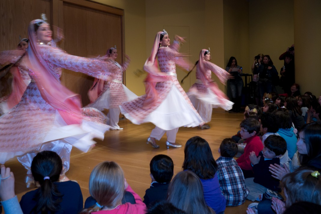 Women dancing on a stage for a crowd to celebrate Nowruz (Flickr/Reed George)