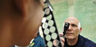 Un paciente mira a través de lentes, en frente de un médico (DOD)