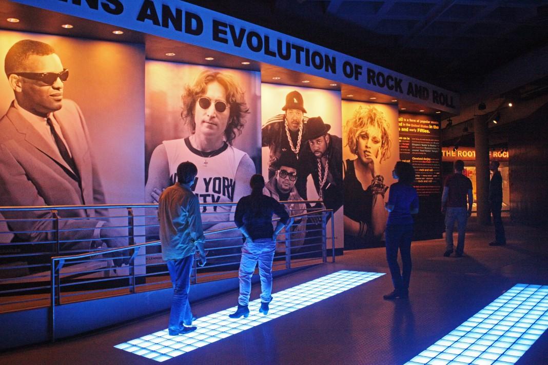 افرادی در موزه به همراه تصاویر بزرگی از مردم (عکس اهدایی از تالار مشاهیر و موزه راک اند رول)