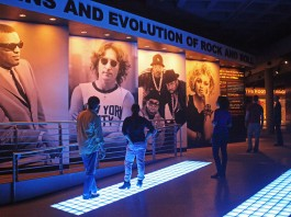 People in museum with large photos of people on wall (Courtesy of Rock and Roll Hall of Fame and Museum Inc.)