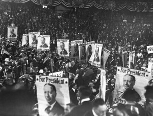 """Convention-goers holding signs reading """"For President"""" (© AP Images)"""