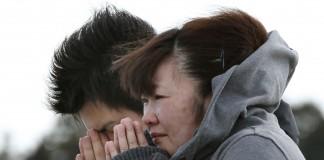 یک زن و مرد ژاپنی با پالتو در هوای آزاد ایستاده و دعا می کنند. (عکس از آسوشیتدپرس)